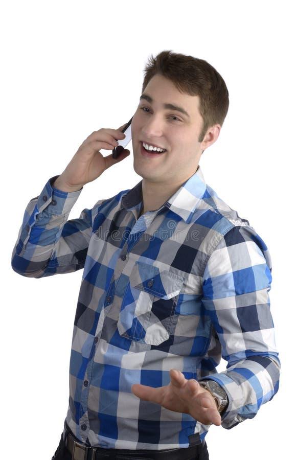 Jonge mens in blauw overhemd die met cellphone spreken stock fotografie