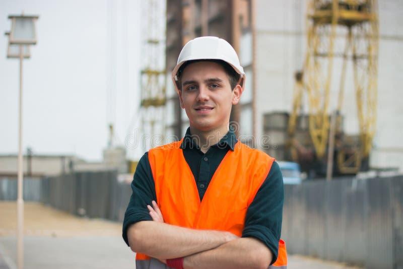 Jonge mens in bouw in oranje vest en helmen stock afbeelding