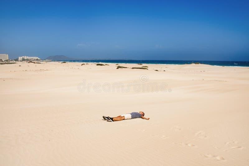 Jonge mens in de duinen in Fuerteventura, Spanje stock fotografie