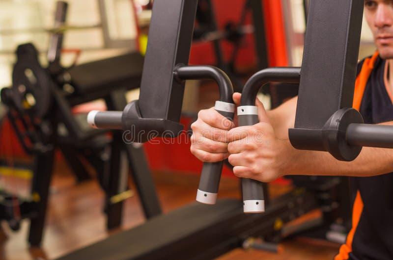Jonge mens in de gymnastiek en het uitoefenen terug op machine royalty-vrije stock fotografie