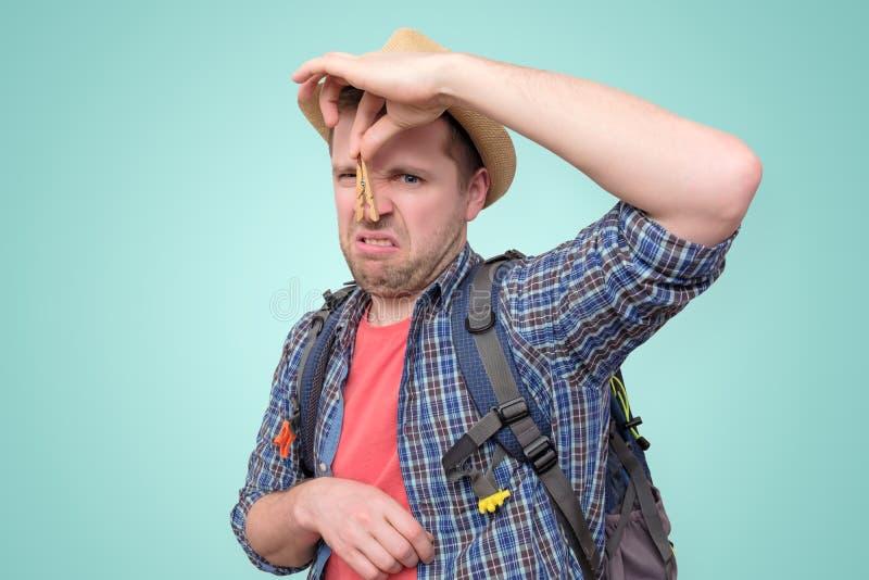 Jonge mens in de zomerhoed met wasknijper op zijn neus royalty-vrije stock foto