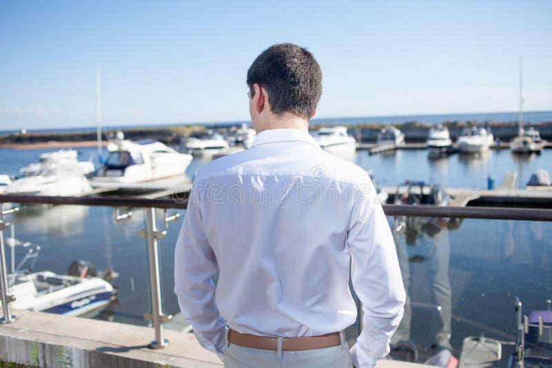 Jonge mens dichtbij de jachtclub, mening van rug royalty-vrije stock foto's