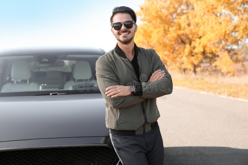 Jonge mens dichtbij moderne auto op zonnige dag l stock fotografie