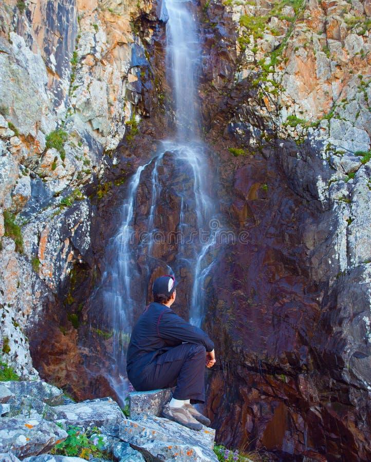 Jonge mens dichtbij waterval in de bergen, ala-Archa, Kyrgyzstan stock fotografie