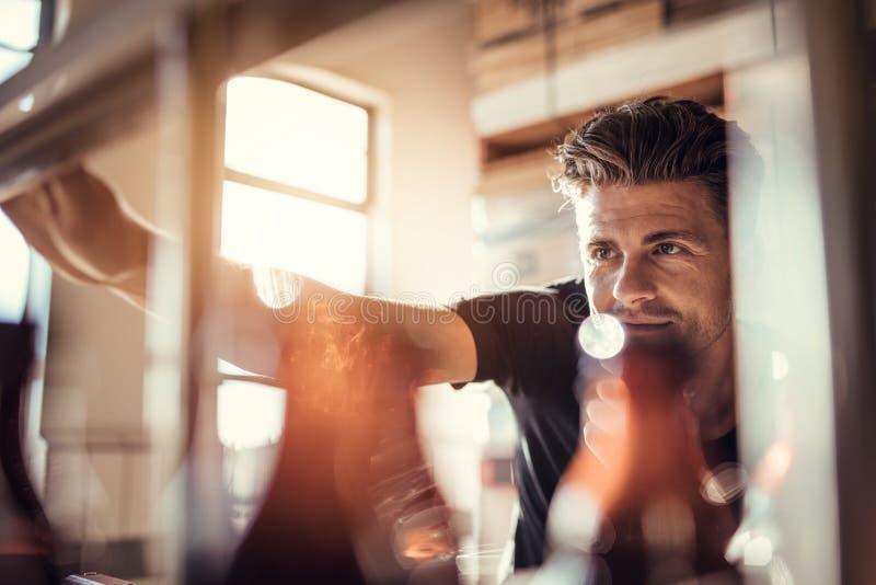 Jonge mens die aan de bier bottelmachine werken royalty-vrije stock afbeelding