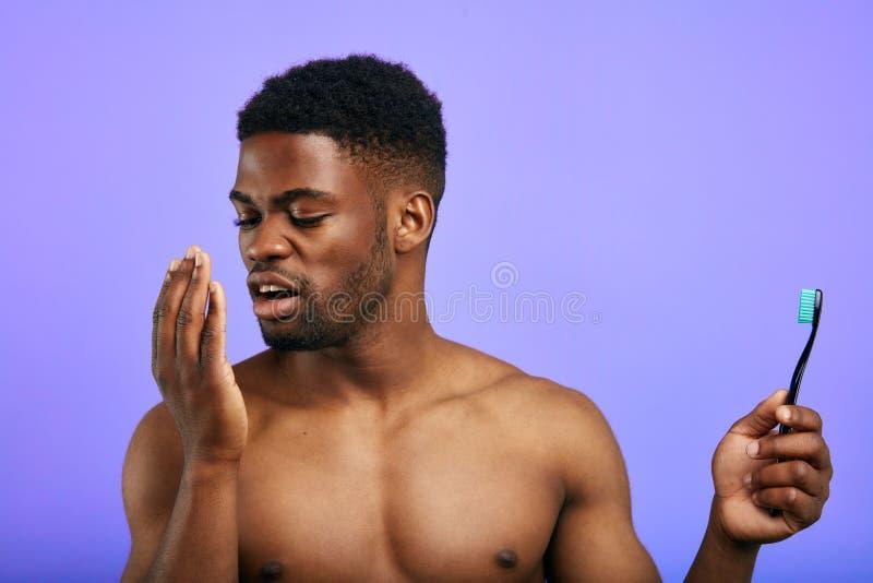 Jonge mens die aan de palm blaast om de geur van zijn mond te weten te komen stock foto
