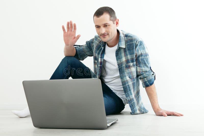 Jonge mens die aan elkaar via online videopraatje spreken Knappe mens die laptop voor zaken en vermaak met behulp van royalty-vrije stock foto's
