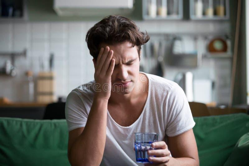Jonge mens die aan hoofdpijn, migraine of kater thuis lijden stock foto