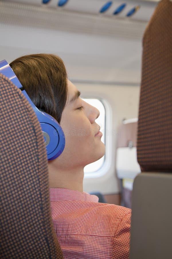 Jonge Mens die aan Hoofdtelefoons luisteren royalty-vrije stock afbeelding