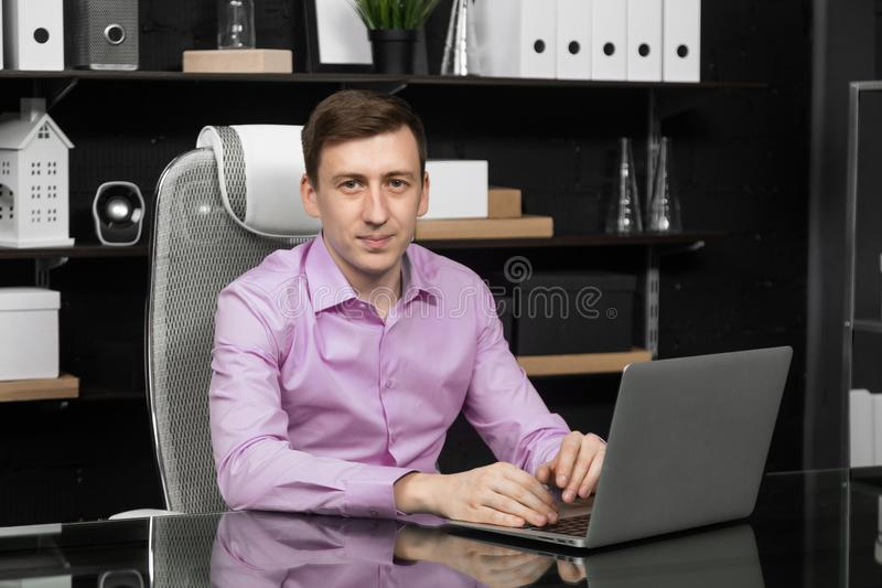 Jonge mens die aan laptop in het bureau werken royalty-vrije stock afbeeldingen