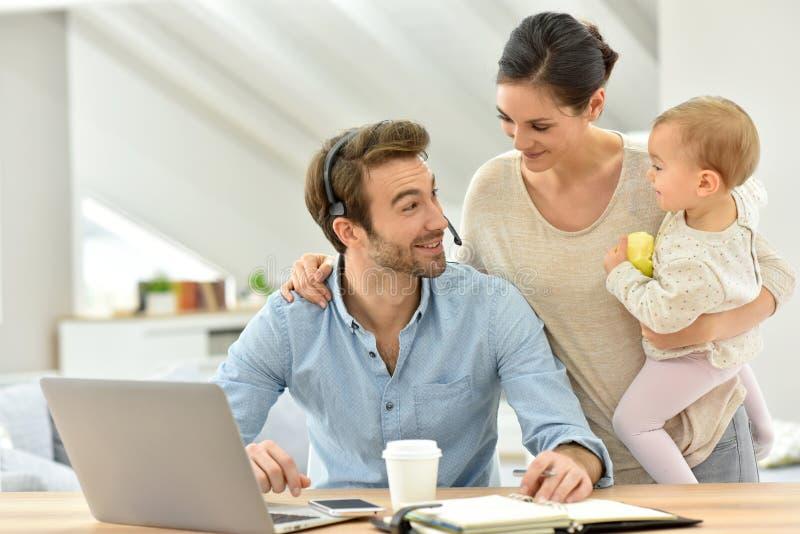 Jonge mens die aan laptop met zijn vrouw en baby werken naast royalty-vrije stock foto's