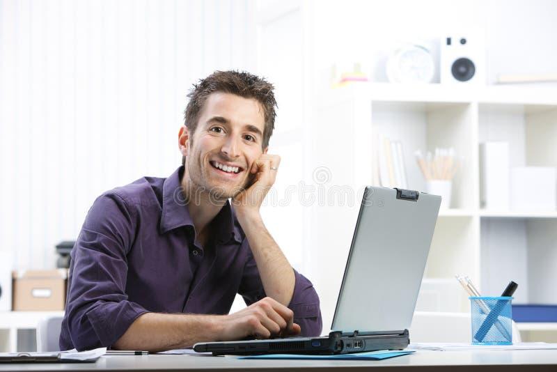 Jonge mens die aan laptop werken stock foto