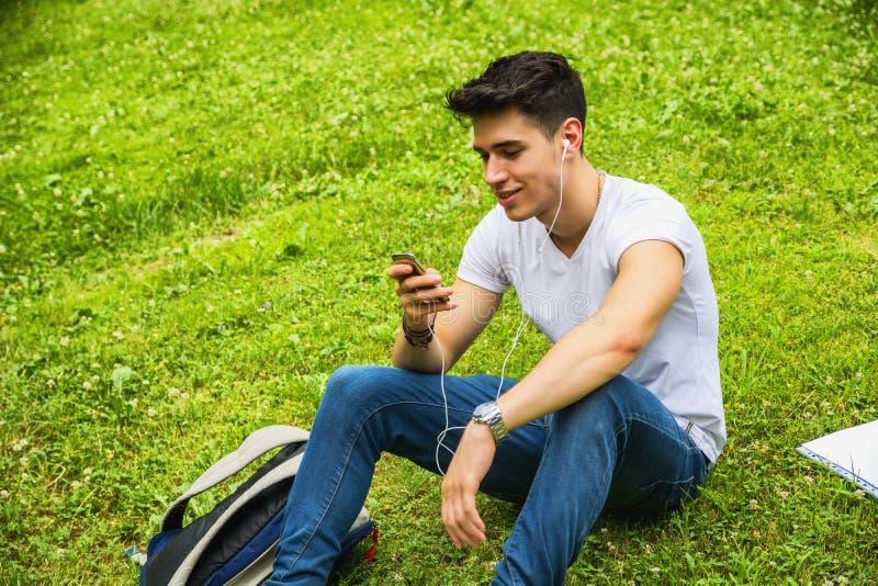 Jonge mens die aan muziek in park luisteren stock afbeelding