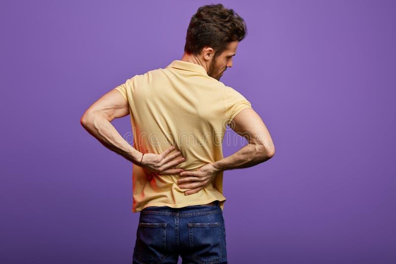 Jonge mens die aan rugpijn lijden stock foto's