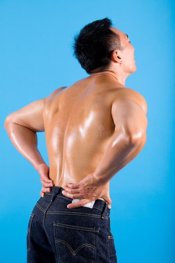 Jonge mens die aan rugpijn lijdt. stock foto's