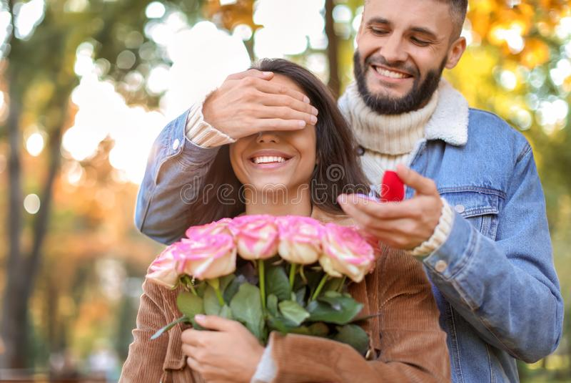 Jonge mens die aan zijn geliefd in de herfstpark voorstellen royalty-vrije stock foto