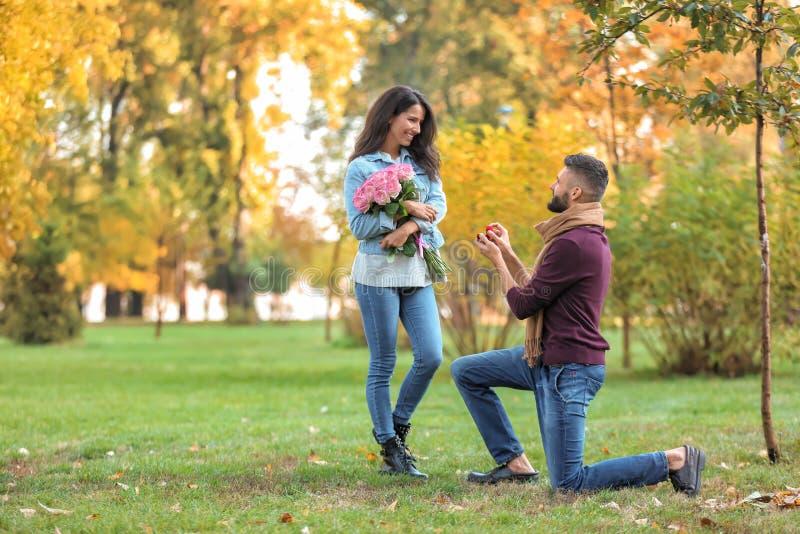 Jonge mens die aan zijn geliefd in de herfstpark voorstellen royalty-vrije stock fotografie