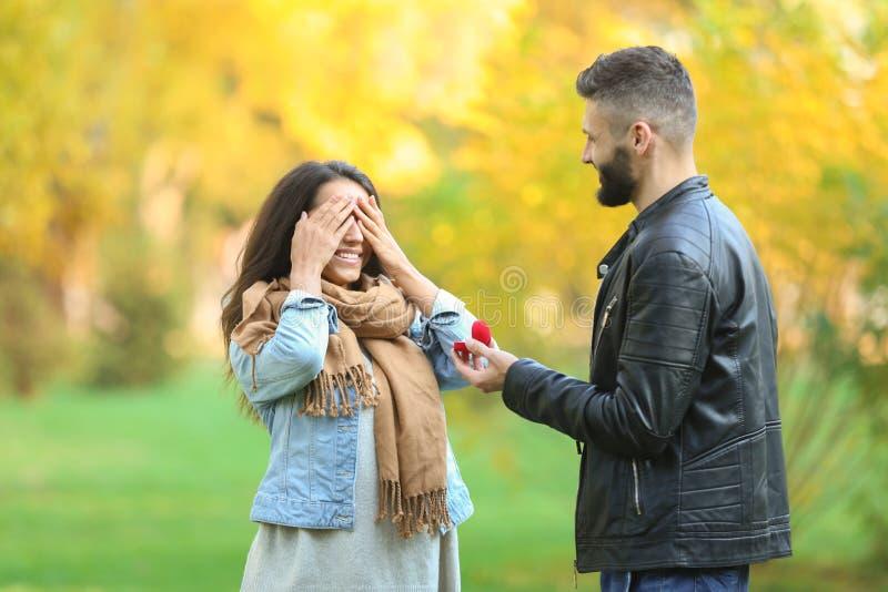 Jonge mens die aan zijn geliefd in de herfstpark voorstellen stock foto's