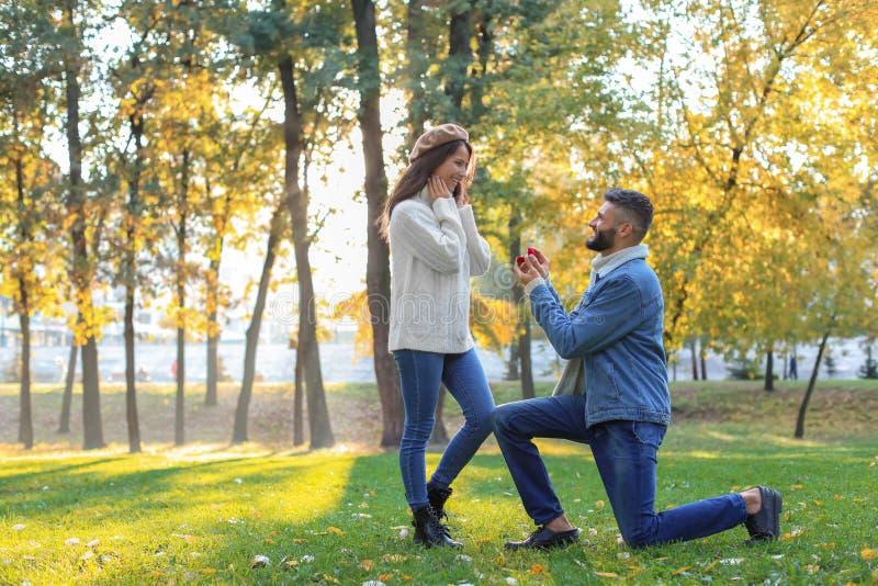 Jonge mens die aan zijn geliefd in de herfstpark voorstellen royalty-vrije stock afbeelding