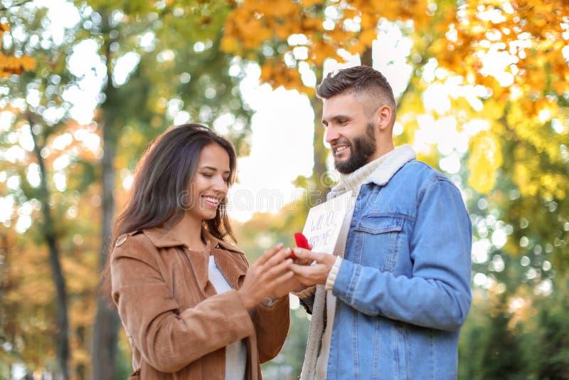 Jonge mens die aan zijn geliefd in de herfstpark voorstellen stock fotografie