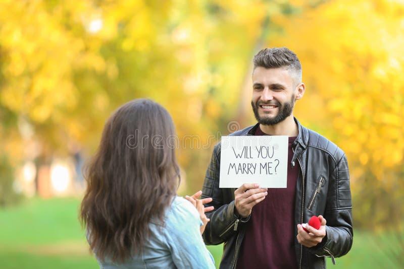 Jonge mens die aan zijn geliefd in de herfstpark voorstellen royalty-vrije stock foto's