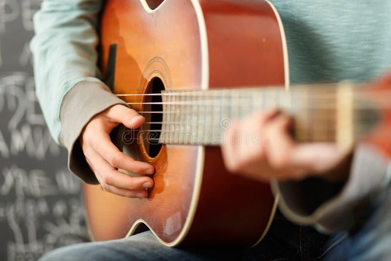Jonge mens die akoestische gitaar spelen royalty-vrije stock foto