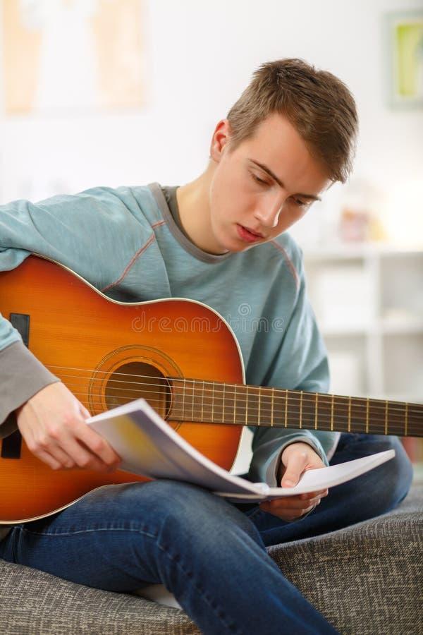 Jonge mens die akoestische gitaar spelen royalty-vrije stock afbeeldingen