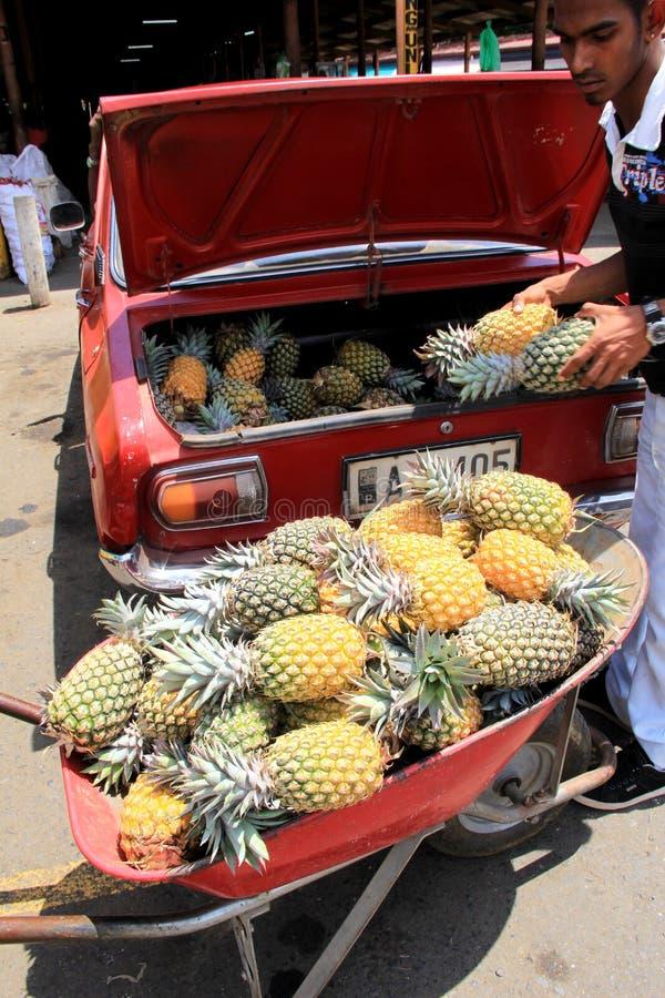 Jonge mens die ananassen verwijderen uit boomstam van auto aan markt, Fiji, 2015 te nemen royalty-vrije stock afbeelding