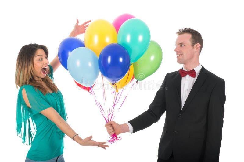 Jonge mens die ballons geven aan meisjesvriend royalty-vrije stock afbeeldingen