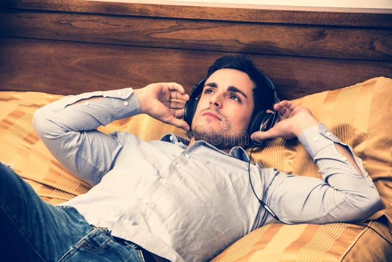Jonge mens die in bed aan muziek met hoofdtelefoons luisteren royalty-vrije stock afbeelding