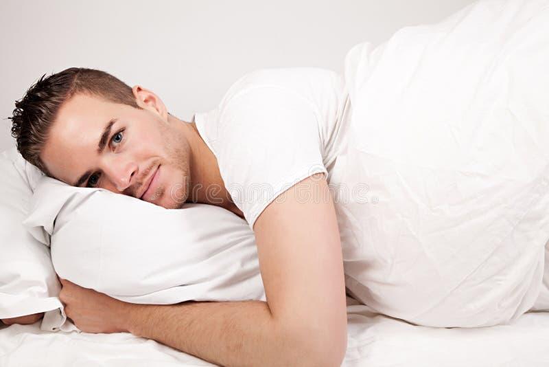 Jonge mens die in bed liggen royalty-vrije stock afbeeldingen
