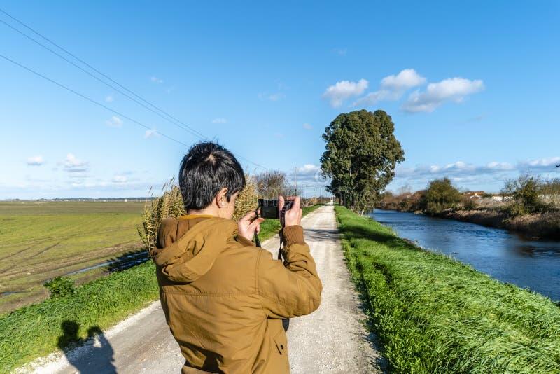 Jonge mens die beeld op natuurlijke achtergrond nemen stock afbeeldingen