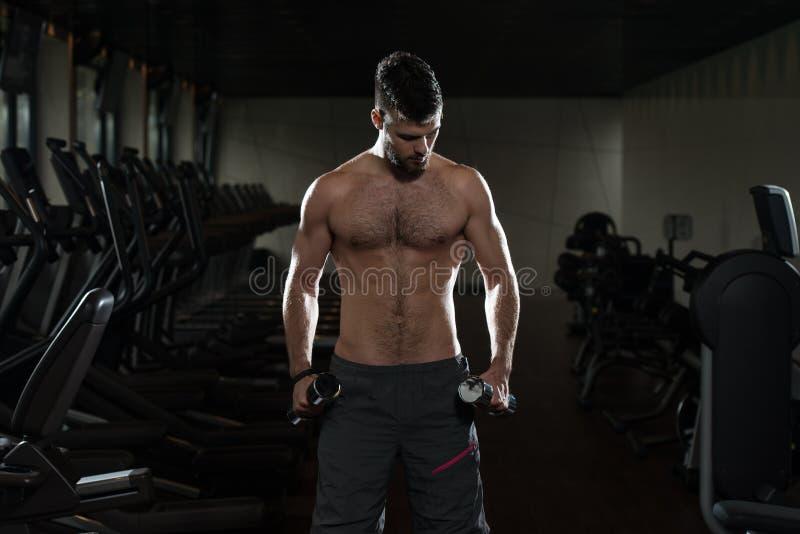 Jonge Mens die Bicepsen met Domoren uitoefenen stock foto's