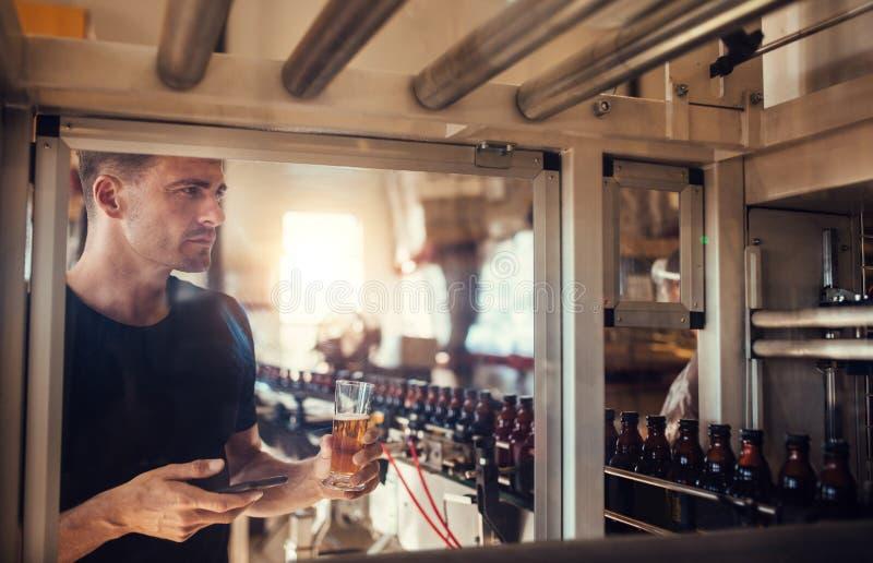 Jonge mens die bier onderzoeken bij brouwerij royalty-vrije stock afbeelding