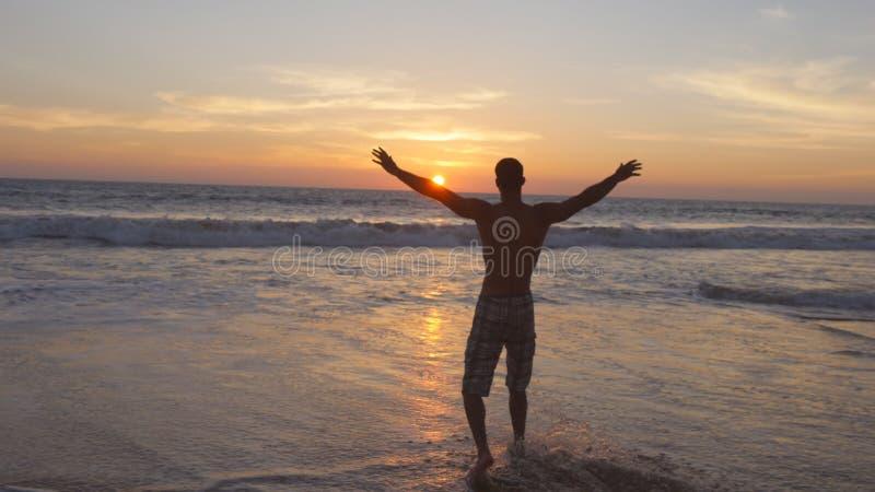 Jonge mens die bij het oceaanwater op strand bij zonsondergang en opgeheven handen lopen Sportieve kerel bevindende op zee kust e royalty-vrije stock foto's