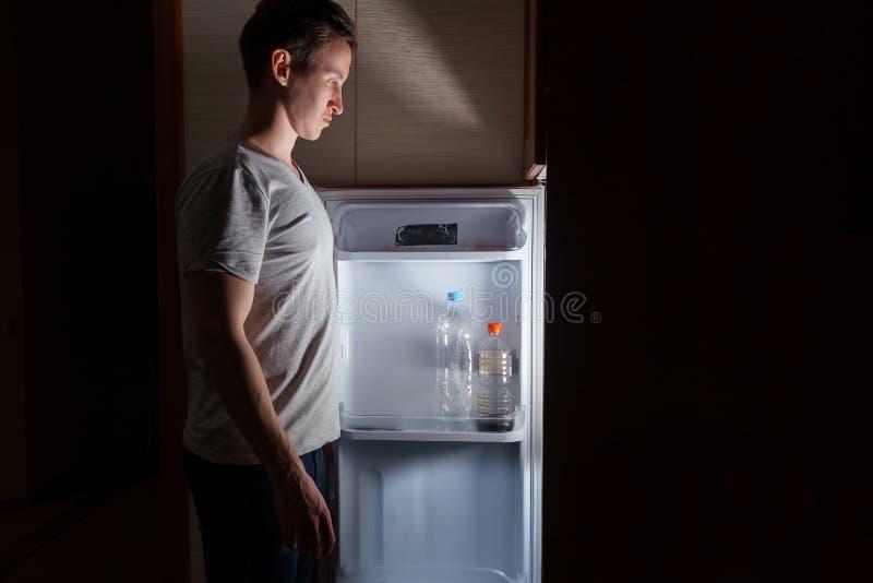 Jonge mens die bij nacht dichtbij de ijskast eten stock afbeelding