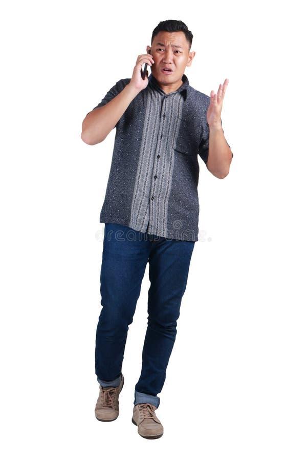 Jonge Mens die bij Telefoon, Geschreeuwde Ongerust gemaakte Uitdrukking spreken stock afbeelding