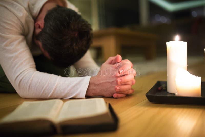 Jonge mens die, Bijbel en kaars naast hem bidden knielen royalty-vrije stock foto's