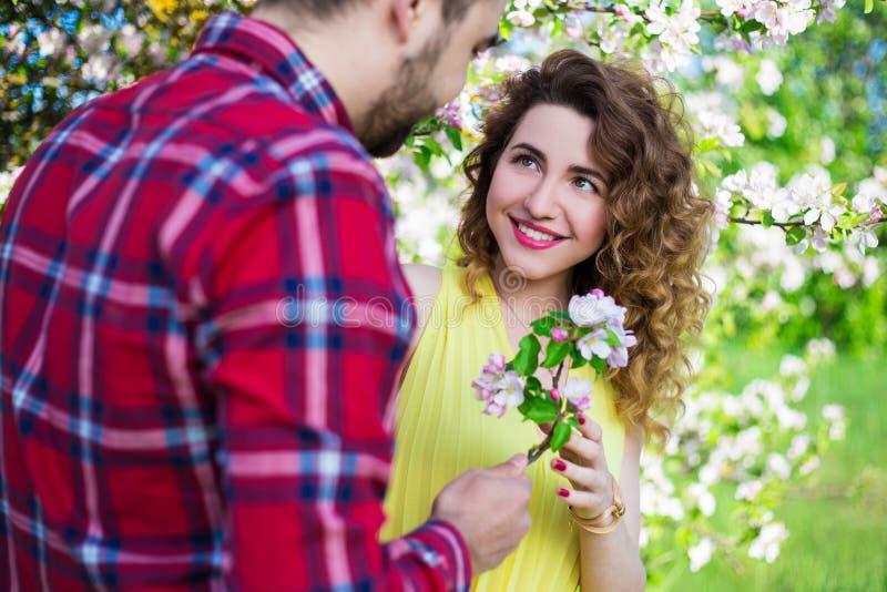 Jonge mens die bloemen geven aan gelukkig meisje in tuin royalty-vrije stock fotografie
