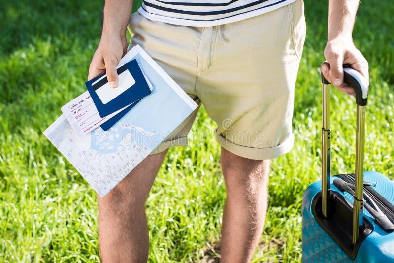 Jonge mens die in borrels koffer, kaart, paspoorten en kaartjes houden terwijl status op groen gazon stock afbeeldingen