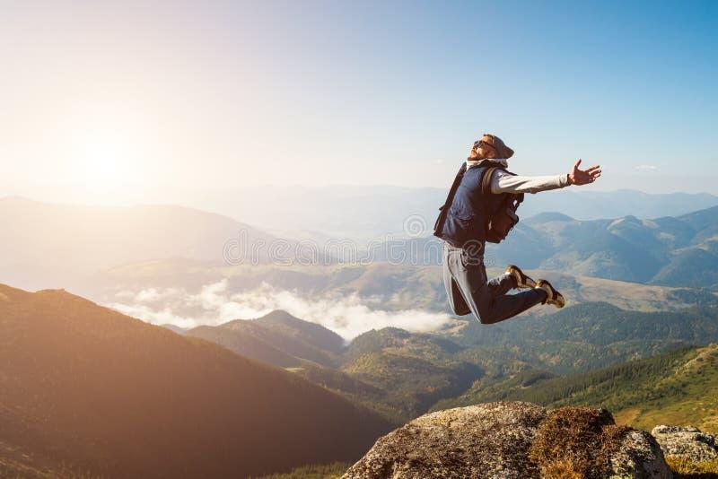 Jonge mens die bovenop een berg tegen de hemel springen stock afbeeldingen