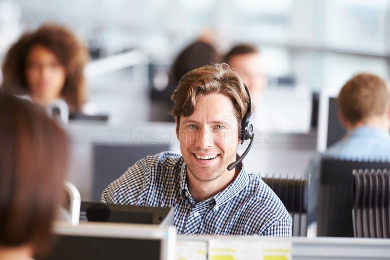 Jonge mens die in call centre werken, die aan camera kijken stock afbeelding