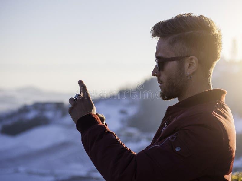 Jonge mens die celtelefoon openlucht op de wintermanier met behulp van stock foto