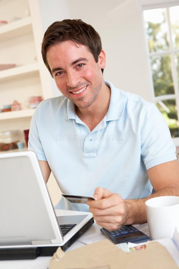 Jonge mens die creditcard op Internet gebruikt stock afbeelding