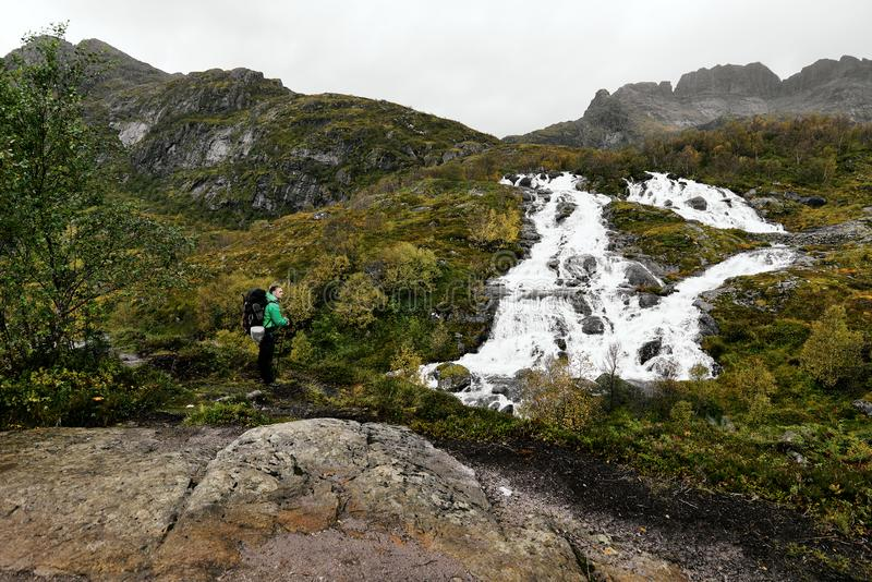 Jonge mens die in de bergen op de Lofoten-Eilanden in Noorwegen wandelen stock foto