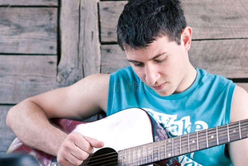 Jonge mens die de gitaar speelt stock fotografie
