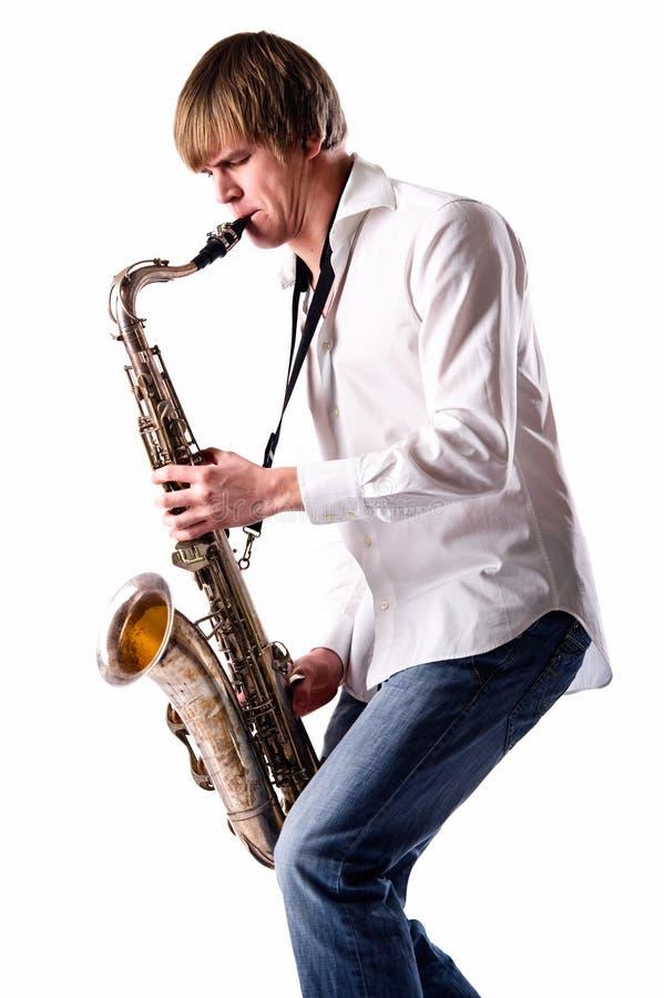 Jonge mens die de saxofoon speelt stock foto