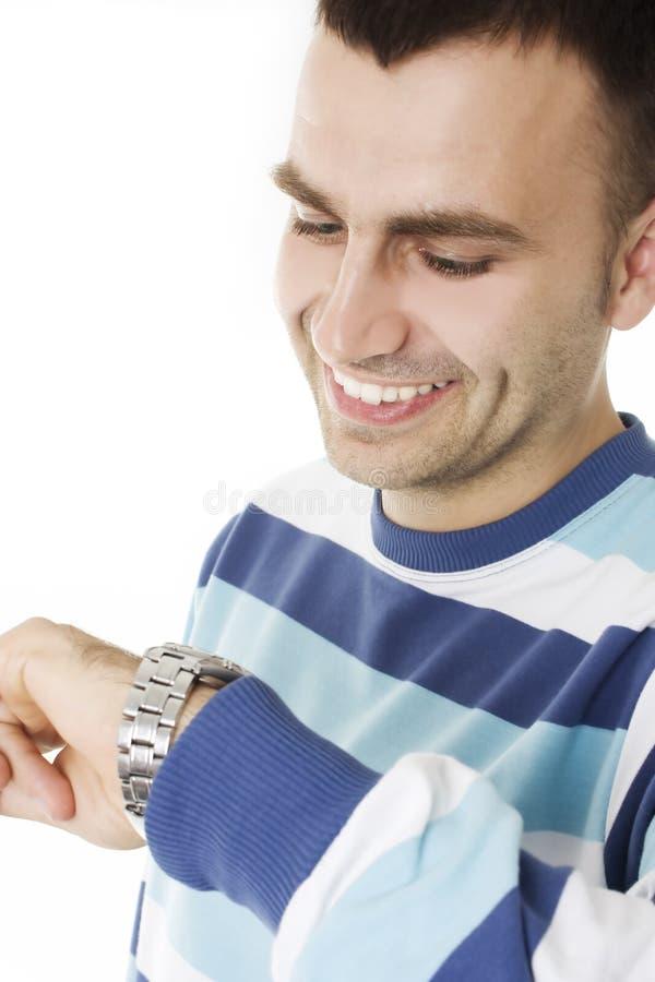 Jonge mens die de tijd in zijn horloge bekijkt stock foto