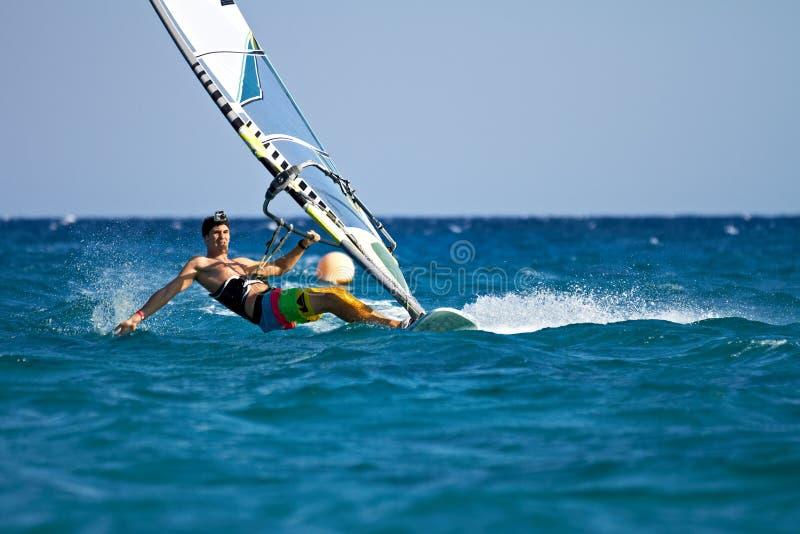 Jonge mens die de wind in plonsen van water surft stock fotografie