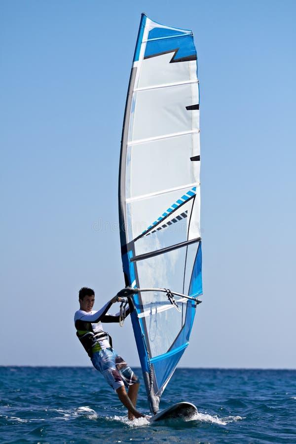 Jonge mens die de wind surft stock foto
